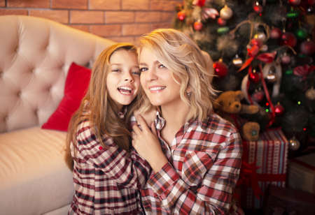 Happy mother and daughter near a Christmas tree fun laughing. Studio photo. Banco de Imagens - 159368677