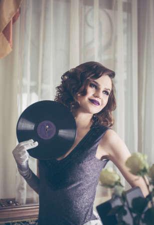 Young beautiful woman in retro style, with a vinyl record. Vintage interior. Studio photo. Banco de Imagens - 159394314
