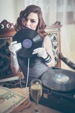 Young beautiful woman in retro style, with a vinyl record. Vintage interior. Studio photo. Banco de Imagens - 159394315