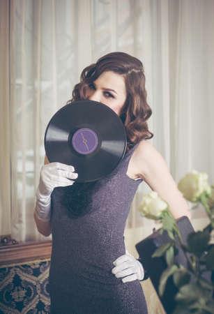 Young beautiful woman in retro style, with a vinyl record. Vintage interior. Studio photo. Banco de Imagens - 159394316