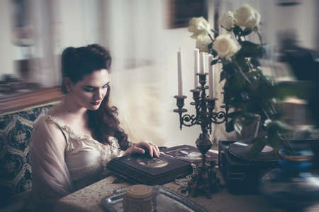 Young woman looks at a photo album. Vintage old style, retro interior.