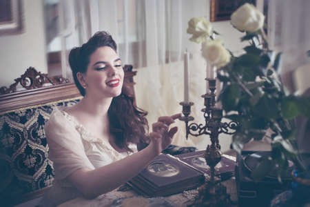 Young woman looks at a photo album. Vintage old style, retro interior. Banco de Imagens - 159393979