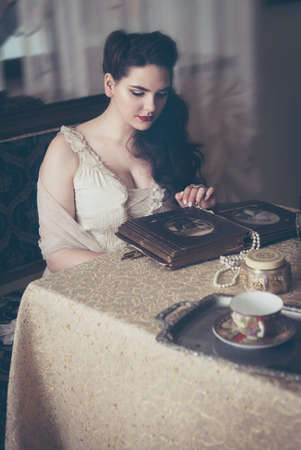 Young woman looks at a photo album. Vintage old style, retro interior. Banco de Imagens - 159393835
