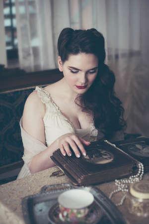 Young woman looks at a photo album. Vintage old style, retro interior. Banco de Imagens - 159394012