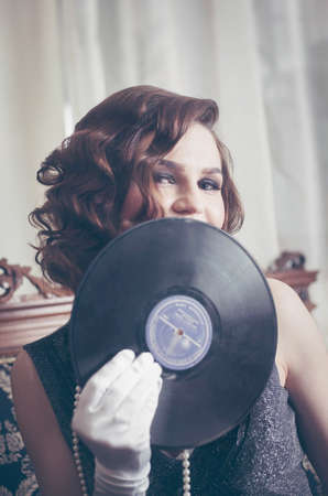 Young beautiful woman in retro style, with a vinyl record. Vintage interior. Studio photo.