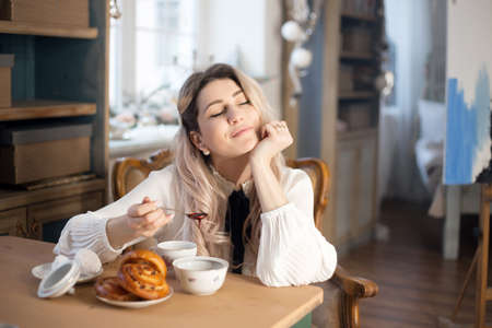 A young woman has breakfast with tea and pastries with jam. Weekend morning. Banco de Imagens - 159394321