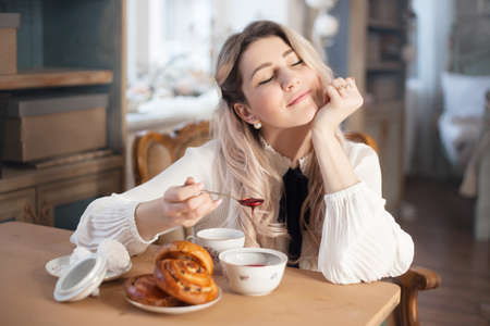 A young woman has breakfast with tea and pastries with jam. Weekend morning.