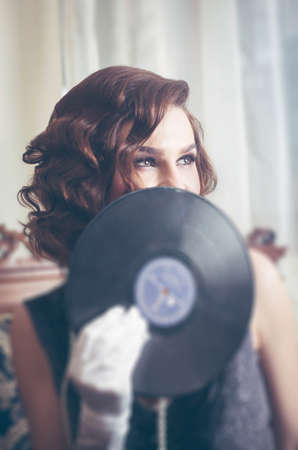 Young beautiful woman in retro style, with a vinyl record. Vintage interior. Studio photo. Banco de Imagens - 159394116