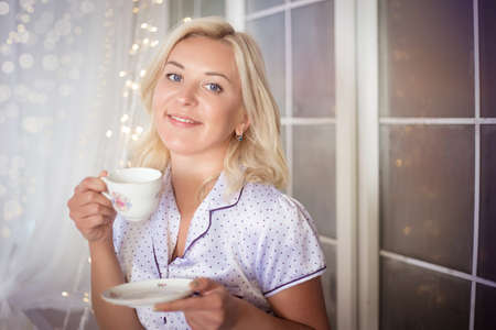 Cute young woman with tea near the window decorated with garlands. A cozy evening at home. Banco de Imagens