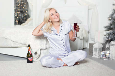 Young beautiful woman in pajamas with champagne in the bedroom. Winter holidays. High quality photo