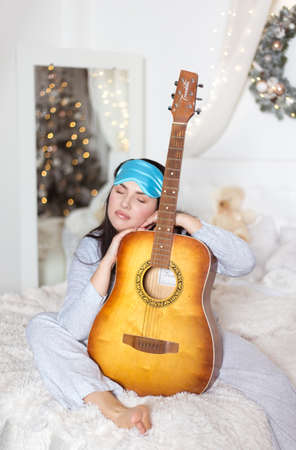 Cute beautiful woman in bed in pajamas with a guitar in her hands. Winter holidays, christmas, studio photo. Stock Photo