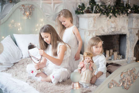 Little girls play in the bedroom in the morning before Christmas. Winter holidays, Christmas, New Year.