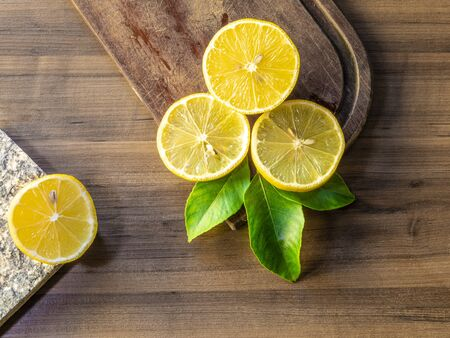 Top view of lemon and green leaves on wooden background