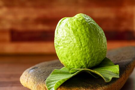 Fresh red guavas with green leaves on wooden demolition background. Wood texture and guava leaves..