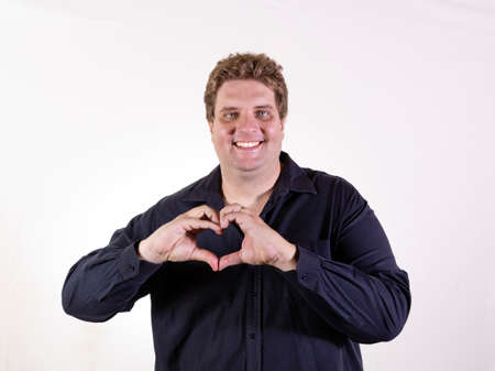 Young curvy man posing in a white background isolated smiling and showing a heart shape with hands