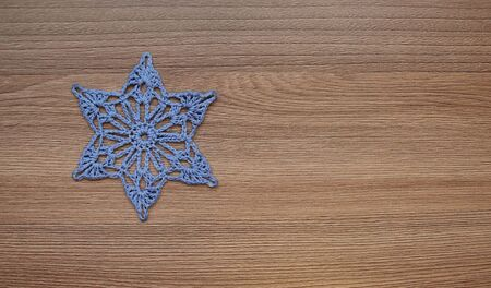 Six-pointed star embroidered from colored threads, on a background of a wooden surface.