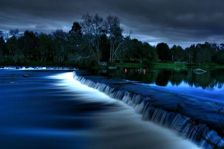 Autumn night waterfall on river