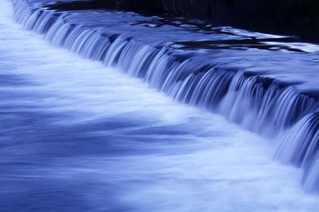 movement of a river waterfall by night photo