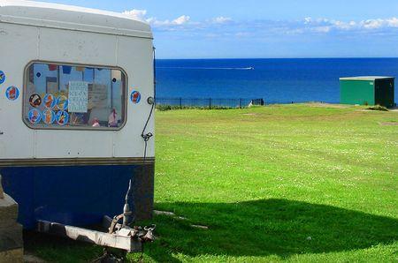 Greem grass field, cloudy blue sky ocean and Ice cream van.