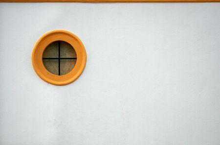 round window: round yellow window ona  white wall Stock Photo