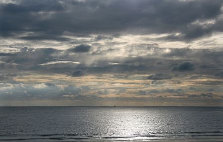 sun on the beach with a boat in the horizon photo