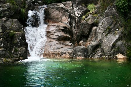 hiden waterfall on a mountain river with a little green lake. Stock Photo - 5326061