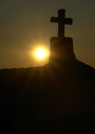 cross shadow behind a sunset on galician town photo
