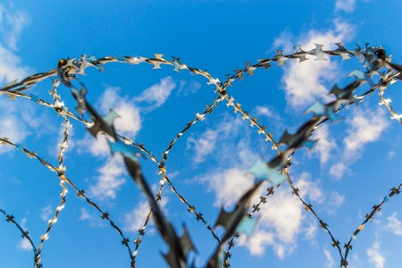Barbed wire against the blue sky