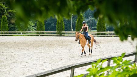 vrouw paardrijden prachtige bruine merrie en trainen in zanderige openlucht manege op paardenboerderij. Stockfoto