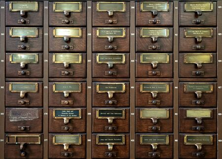 Old vintage wooden archive card library catalog with drawers and metal labels for database and searching information Banco de Imagens
