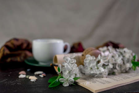 A cup of coffee on a white tray with branch of blossomed cherry and monstera leaf