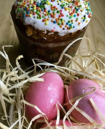Easter cake paska in straw and the colored eggs krashanka