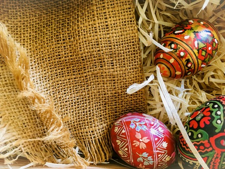 Easter eggs in straw and linen material. Special wood eggs for easter decor. 스톡 콘텐츠