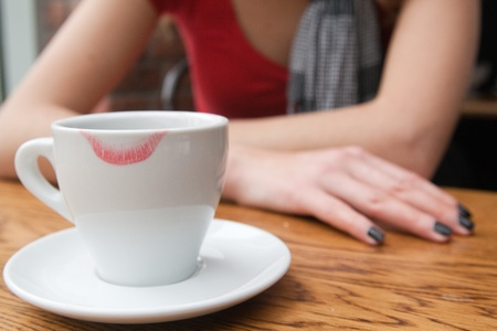 The girl is drinking coffee with a white cup with traces of lipstick photo