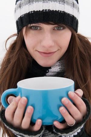 Beautiful girl with a smile, holding a large blue mug