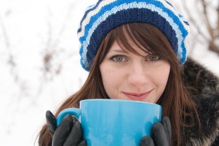 A beautiful young lady holding a large blue mug photo