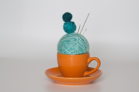 Orange cup with balls of yarn photo