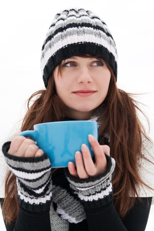 Girl is dreaming and holding a blue cup