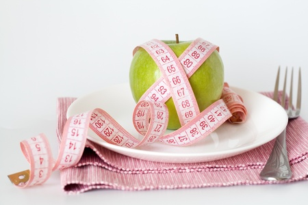 Green apple and measuring tape on a white plate Stok Fotoğraf