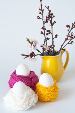 Decorative Easter eggs and a bunch of sprigs of cherry blossoms photo