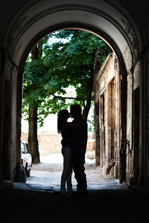 Love young couple kissing in the yard Фото со стока