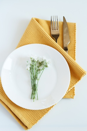 Fork, knife, plate and small white flowers photo