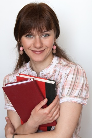 tutorials: Portrait of a young cute student with textbooks in hand Stock Photo