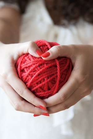 Big ball of red wool in the hands of a girl photo