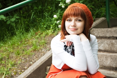Portrait of a young beautiful girl in an orange knitted beret  photo