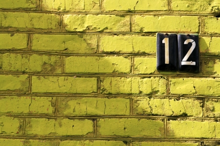 number 12: The brick wall that painted in green color, with the number 12 Stock Photo