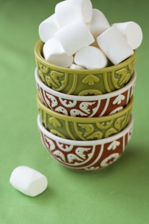 Four oriental national bright bowls on a green background and white marshmallows photo