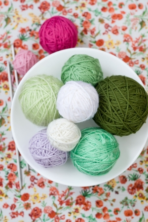 A lot of bright balls of knitting on the background of a red flower Stock Photo