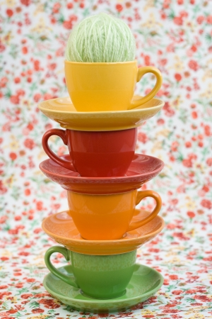Four colorful cups and balls of yarn on a background of a red flower
