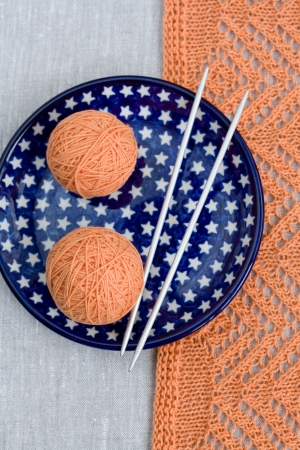 hobie: Two balls of pink yarn and knitting needles on a blue plate